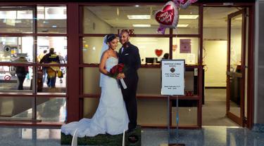 Baner sepasang pengantin dipajang di depan kantor Clark County Clerk's yang melayani jasa layanan untuk pernikahan di Bandara Internasional McCarran di Las Vegas (12/2). Las Vegas dikenal sebagai ibu kota pernikahan dunia. (AFP/L.E. Baskow)