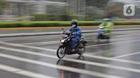 Pengendara sepeda motor menggunakan jas hujan saat berkendara di kawasan Bundaran HI, Jakarta, Minggu (24/1/2021). Kepala BMKG Dwikorita mengatakan, puncak musim hujan akan terjadi pada Januari dan Februari 2021, sehingga perlu diwaspadai terjadinya cuaca ekstrem. (Liputan6.com/Herman Zakharia)