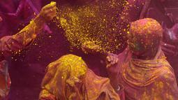 Janda India menaburkan bubuk berwarna-warni saat mengikuti perayaan Holi di kota Vrindavan, India, (9/3). Holi dirayakan di negara India, Nepal, Bangladesh, dan negara dengan pemeluk agama Hindu. (AFP Photo / Dominique Faget)