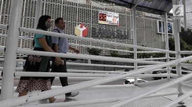 Pejalan kaki melintas di jembatan penyeberangan orang (JPO) dengan latar belakang layar hitung mundur Pemilu 2019 di Gedung Bawaslu, Jakarta, Kamis (21/2). Layar dipasang untuk mengajak masyarakat ikut serta dalam Pemilu 2019. (Merdeka.com/Iqbal Nugroho)