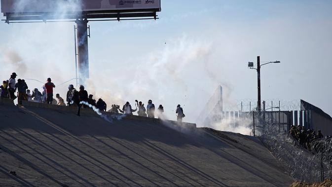Imigran menghindari gas air mata petugas patroli perbatasan AS di dekat pagar pembatas antara Meksiko dan Amerika Serikat di Tijuana, Meksiko (25/11). Walikota Tijuana telah menyatakan krisis kemanusiaan di kota perbatasannya. (AP Photo/Ramon Espinosa)