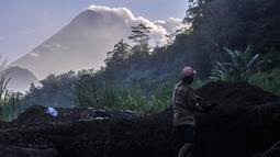Seorang pria bekerja di lokasi penambangan pasir saat Gunung Merapi mengeluarkan abu vulkanik di Yogyakarta, Indonesia, (22/5).  Pihak berwenang juga memerintahkan warga dalam jarak 3 kilometer (2 mil) untuk mengungsi. (AP Photo/Slamet Riyadi)