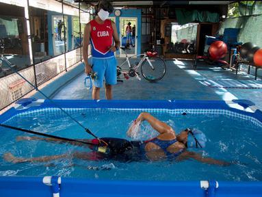 Leslie Amat, seorang atlet triathlon Kuba, berenang di kolam kecil di bawah pengawasan pelatihnya Dioseles Fernandez di teras rumahnya di Havana, Senin (20/4/2020). Atlet Kuba tak bisa berlatih di fasilitas olahraga seperti biasanya selama pademi corona. (AP /Ismael Francisco)