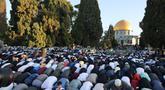 Umat Muslim melaksanakan sholat Idul Fitri di luar masjid Kubah Batu di kompleks masjid Al-Aqsa, Yerusalem Tua (13/5/2021).  Beberapa malam bentrokan antara pengunjuk rasa Palestina dan polisi Israel, terutama di sekitar masjid Al-Aqsa, meningkat awal pekan ini. (AFP/Ahmad Gharabli)