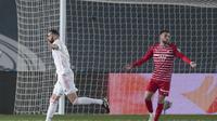 Striker Real Madrid Karim Benzema merayakan golnya ke gawang Granada dalam lanjutan Liga Spanyol di Stadion Alfredo Di Stéfano, Kamis (24/12/2020) dini hari WIB. (AP Photo/Bernat Armangue)