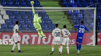 Kiper Real Madrid, Thibaut Courtois, berusaha menghalau bola saat melawan Getafe pada laga Liga Spanyol di Stadion Alfonso Perez, Senin (19/4/2021). Kedua tim bermain imbang 0-0. (AP Photo/Manu Fernandez)