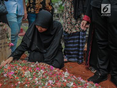 Istri mendiang George Mustafa Taka, Desty Amalia berada di dekat makam suaminya di Komplek Pemakaman Kempo, Jatiwaringin, Pondok Gede, Jakarta, Jumat (2/10). George Mustafa Taka meninggal akibat serangan jantung. (Liputan6.com/Faizal Fanani)