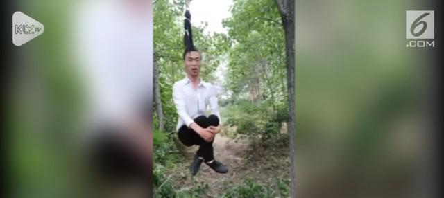 Atraksi dilakukan seorang pria di Provinsi Henan, China. Ia berayun dengan menggunakan rambutnya sepanjang 1,3 meter.