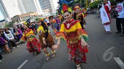 Aksi menari Mahasiswa Universitas Paramadina saat car free day di Bundara HI, Jakarta, Minggu (26/4/2015). Mereka meminta sumbangan kepada warga untuk mengikuti Interntional Folklore Festival di Spanyol. (Liputan6.com/Faizal Fanani)