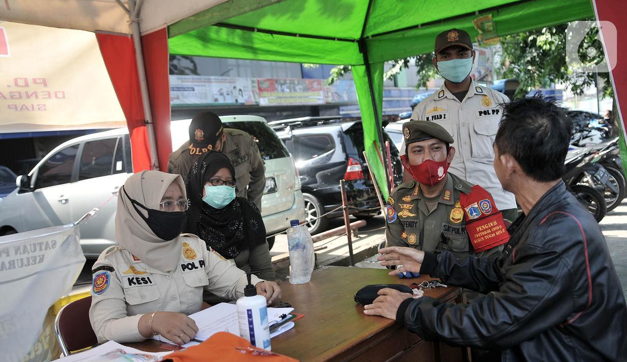 Petugas Satpol PP mendata salah seorang warga yang tidak mengenakan masker di area Pasar Kramat Jati, Jakarta, Rabu (17/6/2020). Petugas memberikan sanksi bagi pelanggar aturan PSBB seperti tidak mengenakan masker di luar rumah berupa denda Rp250 ribu per orang. (merdeka.com/Iqbal S. Nugroho)