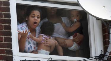 Wanita menggendong bayi menunggu bantuan setelah kebakaran terjadi di dalam gedung apartemen di Hazleton, Pennsylvania (26/7/2019). Pemadam kebakaran kota menggunakan truk menyelamatkan penghuni dari lantai tiga gedung. (Warren Ruda/Hazleton Standard-Speaker via AP)