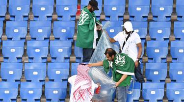Suporter Arab Saudi memunguti sampah di tribun seusai laga melawan Uruguay pada pertandingan kedua Grup A Piala Dunia 2018 di Rostov Arena, Rostov-on-Don, Rabu (20/6). Kalah 0-1, Arab Saudi menjadi tim kedua yang tersingkir setelah Maroko (AFP/JOE KLAMAR)
