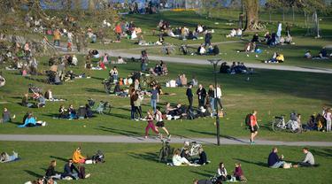 Orang-orang menikmati cuaca hangat di Stockholm, Rabu (22/4/2020). Swedia belum memberlakukan lockdown, seperti mayoritas negara Eropa lainnya, namum pemerintah memberikan tanggung jawab besar kepada penduduknya untuk membantu mengurangi penyebaran virus corona. (Anders WIKLUND/TT NEWS AGENCY/AFP)