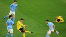 Gelandang Borussia Dortmund, Jude Bellingham (tengah) melepaskan tendangan yang berbuah gol ke gawang Manchester City dalam laga leg kedua perempatfinal Liga Champions 2020/2021 di Signal Iduna Park, Dortmund, Rabu (14/4/2021). Dortmund kalah 1-2 dari Manchester City. (AFP/Wolfgang Rattay/Pool)
