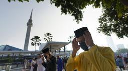 Umat Muslim yang mengenakan masker untuk meredam penyebaran wabah virus corona melaksanakan sholat Idul Fitri menandai akhir bulan suci Ramadhan di luar Masjid Nasional di Kuala Lumpur, Malaysia, Kamis (13/5/2021). (AP Photo/Vincent Thian)
