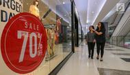 Pengunjung melintasi depan tenant fashion di Lippo Mall Puri, Jakarta, Jumat (24/5/2019). Untuk menarik pengunjung dalam rangka Festival Jakarta Great Sale, berbagai diskon ditawarkan dari pukul 20.00 hingga 00.00 dalam Midsummer Night Sale. (Liputan6.com/Fery Pradolo)