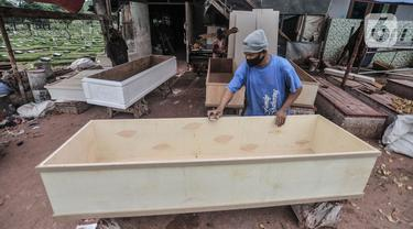 Pekerja menyelesaikan pembuatan peti jenazah di TPU Pondok Kelapa, Jakarta, Selasa (13/7/2021). Melonjaknya angka kematian Covid-19 di Ibu Kota beberapa hari terakhir, menyebabkan jumlah permintaan peti jenazah kembali meningkat hingga membuat pasokan bahan baku menipis (merdeka.com/Iqbal S Nugroho)