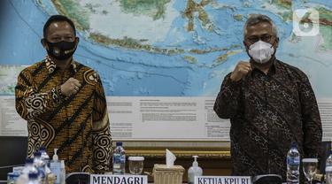 Ketua KPU Arief Budiman (kanan) mendampingi Menteri Dalam Negeri Tito Karnavian (kiri) yang mengunjungi Kantor KPU, Jakarta, Kamis (30/7/2020). Kunjungan Tito Karnavian dalam rangka membahas pelaksanaan Pemilihan Serentak 2020. (Liputan6.com/Johan Tallo)