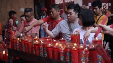 Warga keturunan Tionghoa menyalakan lilin saat bersembahyang Imlek 2569 di Vihara Dharma Bhakti, Petak Sembilan, Jakarta Barat, Jumat (16/2). Imlek 2569 jatuh pada shio anjing atau bisa disebut sebagai tahun anjing. (Liputan6.com/Arya Manggala)
