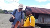 Naftali Fellle menunjukan gerabah di Kampung Abar kepada wisatawan. (Liputan6.com/Katharina Janur)