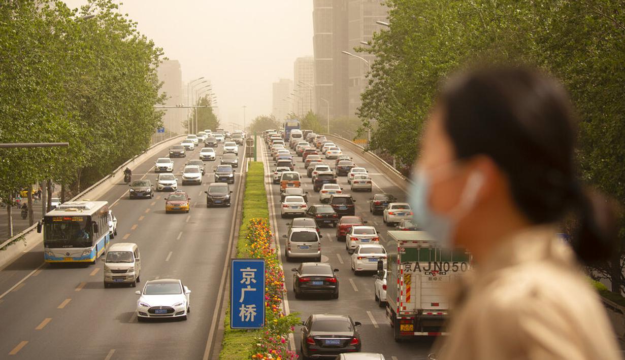 Seorang wanita yang memakai masker wajah berjalan melintasi jembatan penyeberangan saat badai pasir di Beijing, China, Kamis (6/5/2021). Debu dan badai pasir akhir musim semi mengirim indeks kualitas udara melonjak di Ibu Kota China pada hari ini. (AP Photo/Mark Schiefelbein)