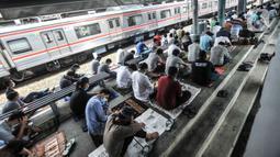 Kereta commuter line melintas dekat jemaah yang tengah salat Jumat di Stasiun Kampung Bandan, Jakarta, Jumat (7/5/2021). Sebagian jemaah menjadikan peron stasiun sebagai tempat salat dan sebagian lain berada di tangga serta jembatan penyeberangan. (merdeka.com/Iqbal S. Nugroho)