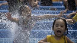 Ekspresi anak-anak saat bermain di kolam portabel yang diberikan oleh pemerintah setempat mendinginkan tubuh pada saat musim panas di Manila, Filipina (12/4). (AFP Photo/Noel Celis)