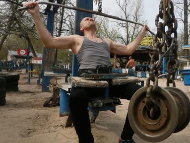Seorang pria berlatih mengangkat beban di outdoor gym atau pusat kebugaran terbuka di tepi Sungai Dnipro, Kiev, Ukraina, Kamis (18/4). Pusat kebugaran terbuka ini terbilang unik karena memanfaatkan besi tua sebagai alat fitness. (AP Photo/Efrem Lukatsky)