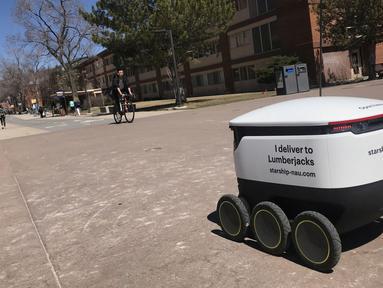 Sebuah robot pengantar makanan melintasi kampus Northern Arizona University di Flagstaff, Arizona, Amerika Serikat, Selasa (26/3). Ada lusinan robot pengantar makanan di kampus ini. (Ben Shanahan/Arizona Daily Sun via AP)