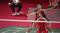 Ganda putri Indonesia Apriyani Rahayu (belakang) dan Greysia Polii mengembalikan kok ke arah wakil Malaysia Chow Mei Kuan dan Lee Meng Yean pada pertandingan pertama Grup A cabang bulu tangkis di Musashino Forest Sport Plaza, Sabtu (24/7/2021). Greysia / Apriyani menang 21-17 (Alexander NEMENOV/AFP)