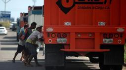 Sejumlah warga mencoba mencuri beras dari truk kargo yang tiba di pelabuhan di Puerto Cabello, Venezuela, Selasa (23/1). Penjarahan sporadis, kerusuhan pangan dan protes yang didorong oleh kelaparan telah melonjak di Venezuela. (AP Photo/Fernando Llano)