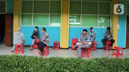 Orangtua murid menunggu untuk pendaftaran daring PPDB tahun ajaran 2021/2022 di Posko Pelayanan PPDB Jakarta Selatan, SMA Negeri 70 Bulungan, Jakarta, Senin (21/6/2021). Pendaftaran PPDB jalur zonasi untuk SMP dan SMA di DKI akan dibuka pada 28 Juni 2021. (Liputan6.com/Herman Zakharia)