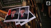 Poster Presiden Joko Widodo dan Wakil Presiden terpilih Ma'ruf Amin yang dijualnya di Pasar Baru, Jakarta, Rabu (16/10/2019). Menjelang pelantikan presiden, foto pasangan Jokowi-Ma'ruf Amin mulaih dijual ke pasar umum. (Liputan6.com/Faizal Fanani)
