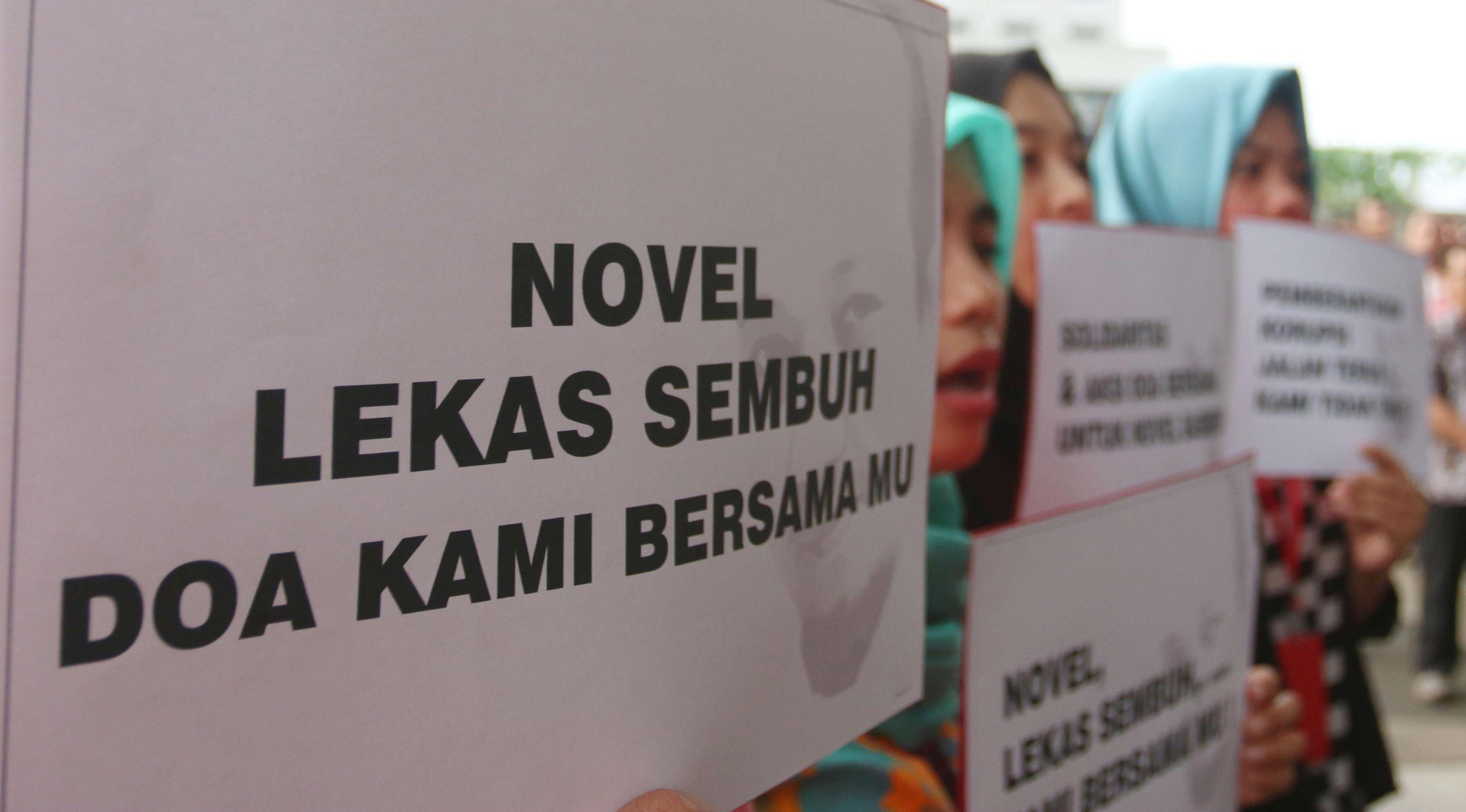Sejumlah orang membawa poster ungkapan kepedulian saat mengikuti aksi peringatan 100 hari penyerangan Novel Baswedan di gedung KPK, Jakarta, Kamis (20/7). (Liputan6.com/Helmi Afandi)
