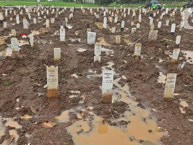 Genangan air terlihat di Taman Pemakaman Umum (TPU) Bambu Apus, Jakarta Timur, Selasa (16/2/2021). Petak makam untuk jenazah korban COVID-19 di TPU Bambu Apus dipersempit dari semula berukuran 2,5 meter x 1,5 meter menjadi 2,2 meter x 1,2 meter per petak makam. (Liputan6.com/Herman Zakharia)