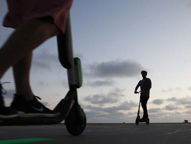 Pengendara menaiki skuter listrik  di sepanjang Venice Beach, Los Angeles, 13 Agustus 2018. Di kota-kota besar di Amerika Serikat, kendaraan listrik telah banyak bermunculan dari berbagai startup. (Mario Tama/Getty Images/AFP)