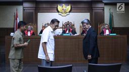 Mantan Wapres, Boediono (tengah depan) usai diambil sumpah saksi pada sidang lanjutan dugaan korupsi penerbitan SKL BLBI dengan terdakwa, Syafruddin Arsyad Temenggung di Pengadilan Tipikor, Jakarta, Kamis (19/7). (Liputan6.com/Helmi Fithriansyah)