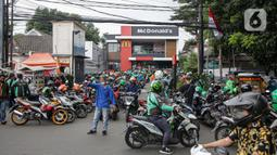 Kerumunan pengemudi ojek online saat antre mengambil pesanan di gerai cepat saji McDonald's Raden Saleh, Jakarta, Rabu (9/6/2021). BTS Meal merupakan menu kolaborasi boyband asal Korea, BTS, dengan McDonald's yang hadir di 50 negara termasuk Indonesia. (Liputan6.com/Faizal Fanani)
