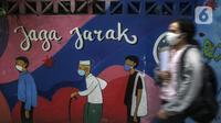 Warga yang mengenakan masker berjalan melintasi mural berisi imbauan terkait COVID-19 di Menteng, Jakarta, Kamis (7/10/2021). Pemerintah menyiapkan langkah implementasi prokes 3M, implementasi surveilans 3T, percepatan vaksinasi dan persiapan fasilitas rumah sakit. (Liputan6.com/Johan Tallo)