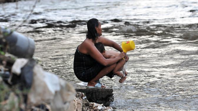 Warga menyeboki anaknya di bantaran Kali Ciliwung, Jakarta, Senin (19/11). Tak adanya akses sanitasi yang layak menyebabkan anak-anak menderita stunting. (Merdeka.com/Iqbal Nugroho)
