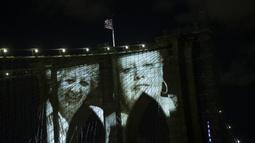 Gambar korban diproyeksikan pada Jembatan Brooklyn saat Hari Peringatan COVID-19 di Brooklyn, New York, Amerika Serikat, 14 Maret 2021. Upacara penghormatan yang digelar secara virtual itu dimulai dengan pertunjukan di Jembatan Brooklyn yang ikonik. (Kena Betancur/AFP)