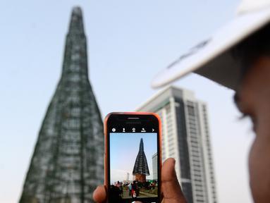 Seorang pria Sri Lanka mengambil foto pohon Natal di Kolombo, Sabtu (24/12). Tingginya yang mencapai 50 meter ini dinobatkan sebagai pohon natal tertinggi di dunia. (AFP PHOTO / Lakruwan Wanniarachchi)