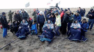 Astronot AS Kate Rubins, kosmonot Rusia Anatoly Ivanishin, dan astronot Jepang Takuya Onishi beristirahat setelah berhasil mendarat di daerah terpencil sekitar 150 km sebelah tenggara dari Dzhezkazgan, Kazakhstan (30/10). (Reuters/Dmitri Lovetsky)
