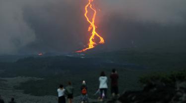 Warga melihat guguran lava pijar yang keluar dari gunung api Piton de la Fournaise atau Peak of the Furnace di Pulau Reunion, Samudera Hindia, Prancis, Selasa (13/8/2019). Letusan Piton de la Fournaise berlanjut hingga hari ketiga. (Richard BOUHET/AFP)