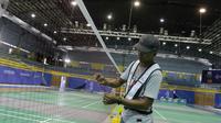 Pekerja sedang memasang net bulutangkis di Muntinlupa Sports Center menjelang SEA Games 2019, Sabtu (23/11/2019). (Bola.com/Muhammad Iqbal Ichsan)