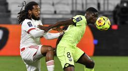 Bek Olympique Lyon, Jason Denayer, berebut bola dengan gelandang Dijon, Eric Junior Dina-Ebimbe, pada laga Ligue 1 di Stadion Groupama, Sabtu (29/8/2020) dini hari WIB. Lyon menang 4-1 atas Dijon. (AFP/Philippe Desmazes)