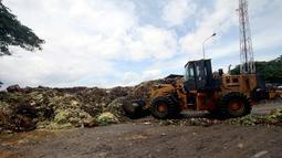 Petugas membersihkan sampah yang menggunung dengan mengunakan alat berat  di Pasar Induk Kramat Jati, Jakarta, Kamis (8/1/2015). (Liputan6.com/Faizal Fanani)