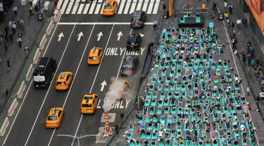 Sejumlah orang melakukan yoga bersama di kawasan Times Square, New York pada 'Summer Solstice' atau hari dengan siang terpanjang di musim panas, Rabu (21/6). Acara tersebut menandai Hari Yoga Internasional yang jatuh pada 21 Juni. (TIMOTHY A. CLARY/AFP)