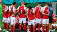 Pemain Denmark mengelilingi tim medis yang tengah merawat Christian Eriksen pada laga melawan Finlandia di Euro 2020, Sabtu (12/6/2021). (AFP/Wolfgang Rattay)