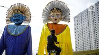 Sejumlah pekerja merapikan ondel-ondel yang dipasang di Taman Ismail Marzuki (TIM), Jakarta, Selasa (22/6/2021). Sebanyak 10 ondel-ondel raksasa setinggi 4,94 meter akan dipamerkan di TIM saat peringatan HUT ke-494 DKI Jakarta yang berlangsung dari 22 hingga 30 Juni 2021 (Liputan6.com/Faizal Fanani)